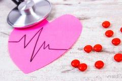 Coeur de papier avec la ligne de cardiogramme, pilules de stéthoscope et de supplément, médecine et concept de soins de santé Images libres de droits
