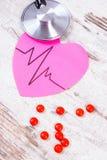 Coeur de papier avec la ligne de cardiogramme, pilules de stéthoscope et de supplément, médecine et concept de soins de santé Photo stock