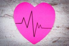Coeur de papier avec la ligne de cardiogramme sur le concept en bois de fond, de médecine et de soins de santé Photographie stock