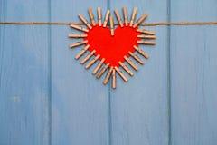 Coeur de papier de l'amour avec les agrafes en bois sur la corde sur le fond en bois bleu Images libres de droits
