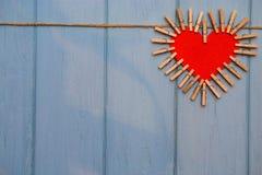 Coeur de papier de l'amour avec les agrafes en bois sur la corde sur le fond en bois bleu Image libre de droits