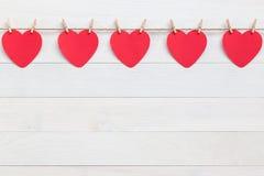 Coeur de papier rouge accrochant sur la corde brune de nature avec le mini clothespi Photos libres de droits
