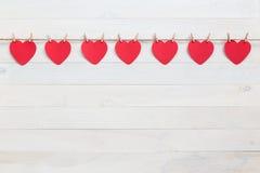 Coeur de papier rouge accrochant sur la corde brune de nature avec le mini clothespi Photographie stock libre de droits