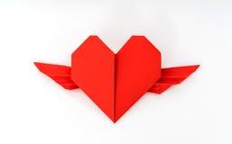 Coeur de papier rouge d'origami avec des ailes sur le fond blanc Images stock