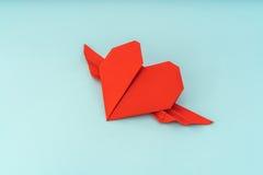 Coeur de papier rouge d'origami avec des ailes sur le fond bleu Images stock