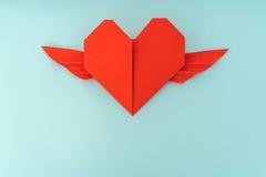 Coeur de papier rouge d'origami avec des ailes sur le fond bleu Image libre de droits