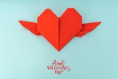 Coeur de papier rouge d'origami avec des ailes sur le fond bleu Photos stock