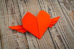 Coeur de papier rouge d'origami avec des ailes sur le fond en bois Photo libre de droits