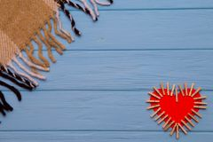 Coeur de papier rouge de l'amour avec des agrafes sur le fond en bois bleu Photo stock