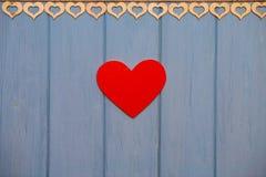 Coeur de papier rouge de l'amour avec des agrafes sur le fond en bois bleu Photos stock
