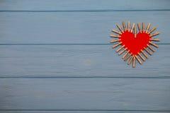 Coeur de papier rouge de l'amour avec des agrafes sur le fond en bois bleu Image libre de droits