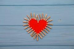 Coeur de papier rouge de l'amour avec des agrafes sur le fond en bois bleu Image stock