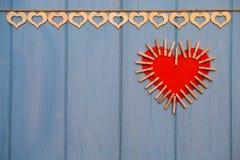 Coeur de papier rouge de l'amour avec des agrafes sur le fond en bois bleu Images libres de droits