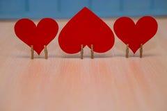 Coeur de papier rouge de l'amour avec les agrafes en bois sur la table avec le fond en bois bleu Photo stock