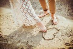 Coeur de peinture de jambes de couples sur le sable Photos libres de droits