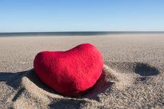 Coeur de peluche sur le sable sous le soleil étouffant Images stock