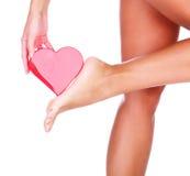 Coeur de pied et de rouge du ` s de femme Photographie stock