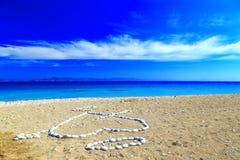 Coeur de pierre, et les premières lettres des noms présentés sur le rivage de Pebble Beach Image libre de droits