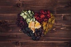 Coeur de plan rapproché sec de fruits sur le fond en bois brun Composition décorative pour le jour du ` s de Valentine Images stock