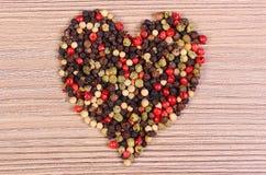 Coeur de poivre coloré frais sur le fond en bois Photo libre de droits