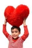 Coeur de rouge d'oreiller de prise de petit garçon Photo stock