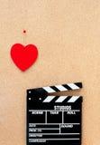 Coeur de Saint-Valentin et panneau de clapet de film sur le backgrou en bois Photographie stock libre de droits