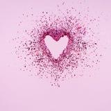 Coeur de scintillement se dissolvant dans des morceaux sur le fond rose Jour de valentines, coeur brisé et concept d'émergence d' photos libres de droits