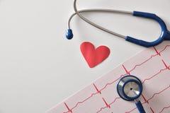 Coeur de stéthoscope et de coupe-circuit d'électrocardiogramme sur la table blanche à Photos libres de droits