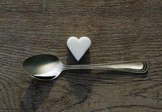 Coeur de sucre blanc avec une cuillère de thé sur le fond en bois Image stock