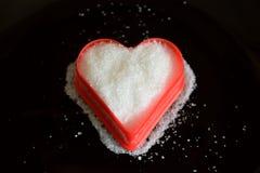 Coeur de sucre rouge et blanc sur le fond noir Photos libres de droits