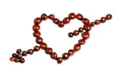 Coeur de symbole avec la flèche faite de châtaignes Photos libres de droits
