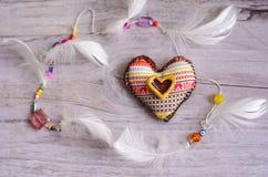 Coeur de textile de fait main avec l'ornement ethnique sur un vieux fond âgé grisâtre élément décoratif des plumes blanches Hea e Photo libre de droits