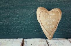Coeur de tissu de vintage sur la table en bois devant le tableau noir Photographie stock