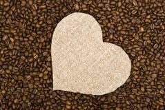 Coeur de toile à sac sur des grains de café Photographie stock libre de droits