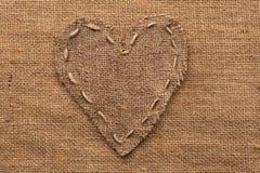 Coeur de toile de jute, mensonges sur un fond de toile de jute Photographie stock libre de droits