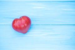Coeur de tomate sur une table bleue Photos libres de droits