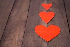 Coeur de trois rouges sur le fond du vieux bois Image stock