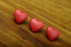 Coeur de trois rouges sur le fond en bois Photographie stock libre de droits
