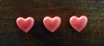 Coeur de trois rouges sur le fond en bois Photo libre de droits