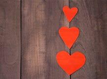 Coeur de trois rouges sur le fond en bois brun Photo stock