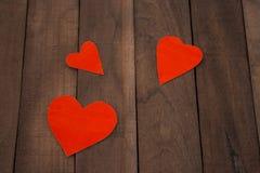 Coeur de trois rouges sur le fond en bois brun Photographie stock