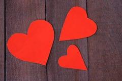 Coeur de trois rouges sur le fond en bois brun Photographie stock libre de droits
