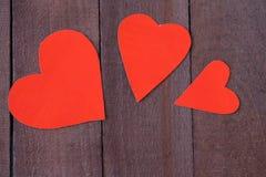 Coeur de trois rouges sur le fond en bois brun Photos stock