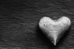 Coeur de Valentine Metal sur un panneau de granit Le coeur argenté de Valentine deux avec des ornements Coeur des valentines et d Photographie stock libre de droits