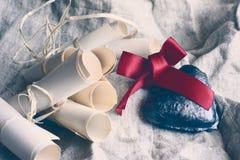 Coeur de valentines avec le ruban cramoisi et les rouleaux de papier, fond rustique de tissu Filtre de style de vintage Photo stock