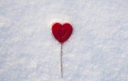 Coeur de Valentines du bonbon un fait de sucre avec l'effet de réflexion sur la neige photographie stock libre de droits