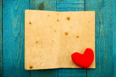 Coeur de vintage et un vieux livre vide sur le fond en bois Photo libre de droits