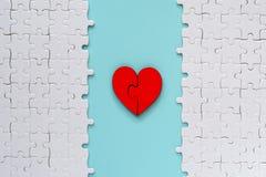 Coeur denteux rouge en deux pièces d'amour avec le puzzle blanc sur le fond bleu Image libre de droits