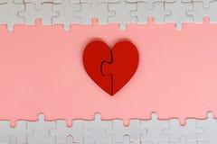 Coeur denteux rouge en deux pièces d'amour avec le puzzle blanc sur le fond rose Image stock