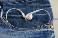 Coeur des écouteurs blancs - un symbole de l'amour piaule hors de la poche de pantalons de jeans Amour pour la musique Le concept Images libres de droits